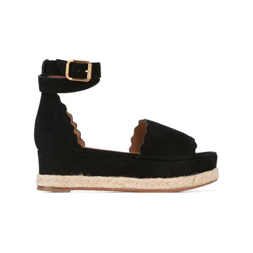 Sandália plataforma de couro 'Lauren' preta, Chloé. Possui fechamento por alça com fivela no tornozelo, detalhes ondulad...