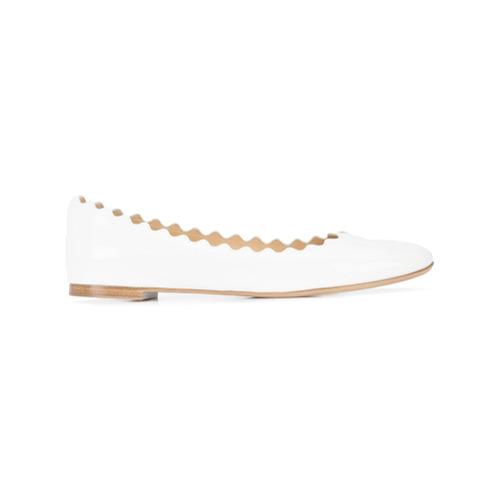 Sapatilha 'Lauren' de couro envernizado branca, Chloé. Possui estilo slip-on, bico arredondado, detalhes ondulados, salt...